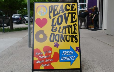 A sign in front of the Peace, Love, and Little Donuts storefront advertises the newly opened business. Peace, Love, and Little Donuts recently opened at 632 College Avenue.