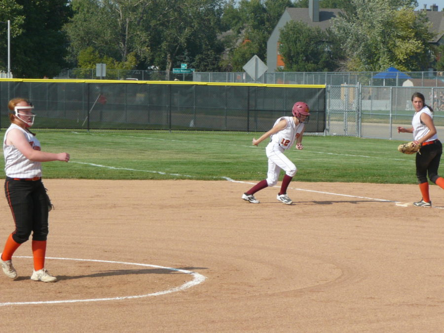 Evee Caramanno dives back to first base.