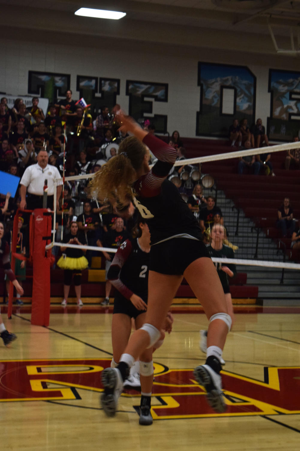 Player India Young, junior, hits the ball onto the other side of the court.