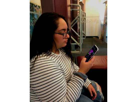 This student plays a game  on her phone while at school, as do many students.