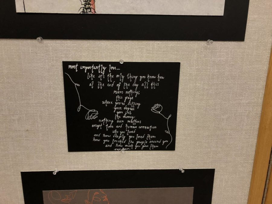 Fiona Nelson, senior, adds quotes to her display to capture the love she feels for art.