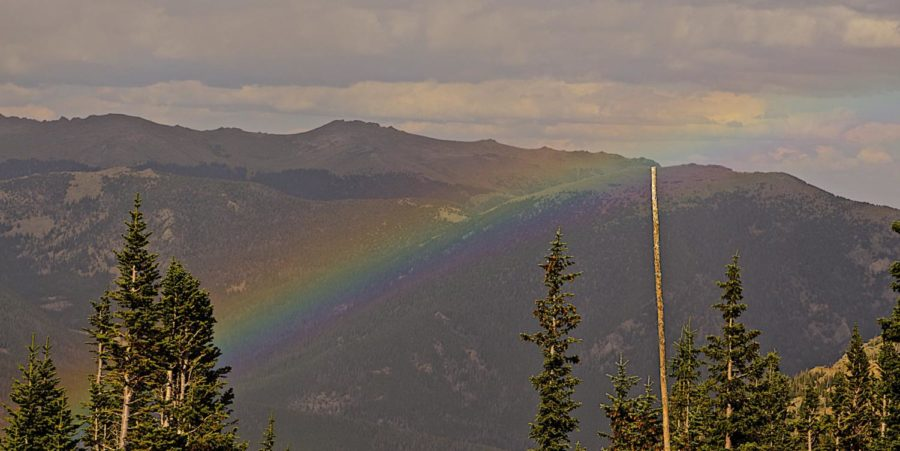 A rainbow falls over the Rocky Mountains.