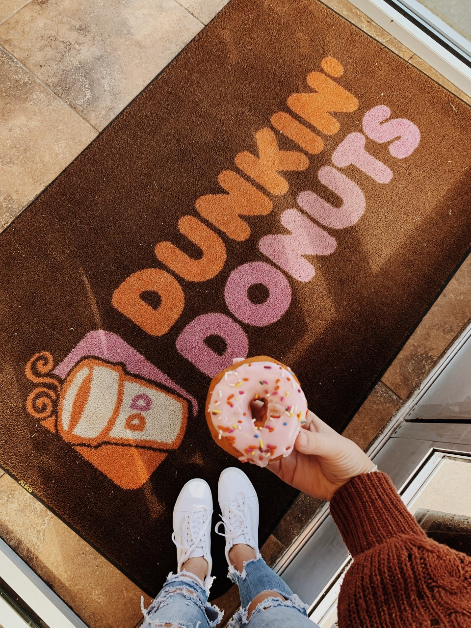 Pictured here is the Dunkin' Donuts entry way mat and a strawberry iced donut.